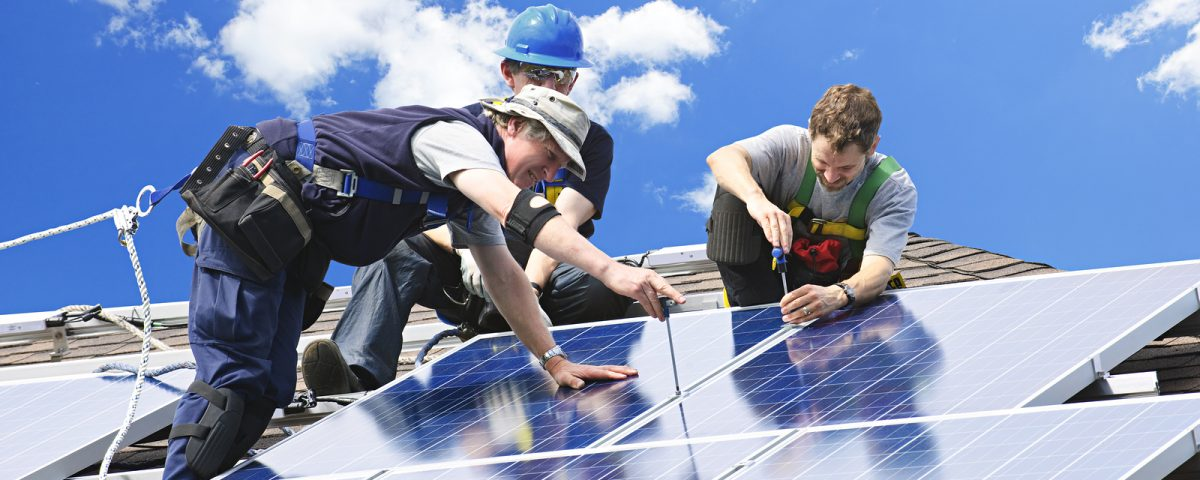 Workers installing alternative energy photo-voltaic solar panels on roof